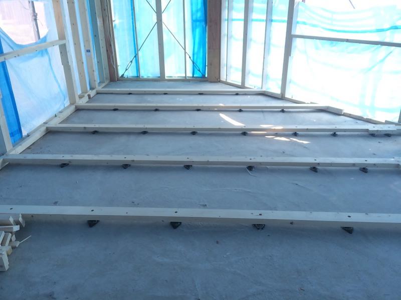 2階床下工事、天井高が低いため下地調整用の束の上に施工、24㎜の下地合板を施工