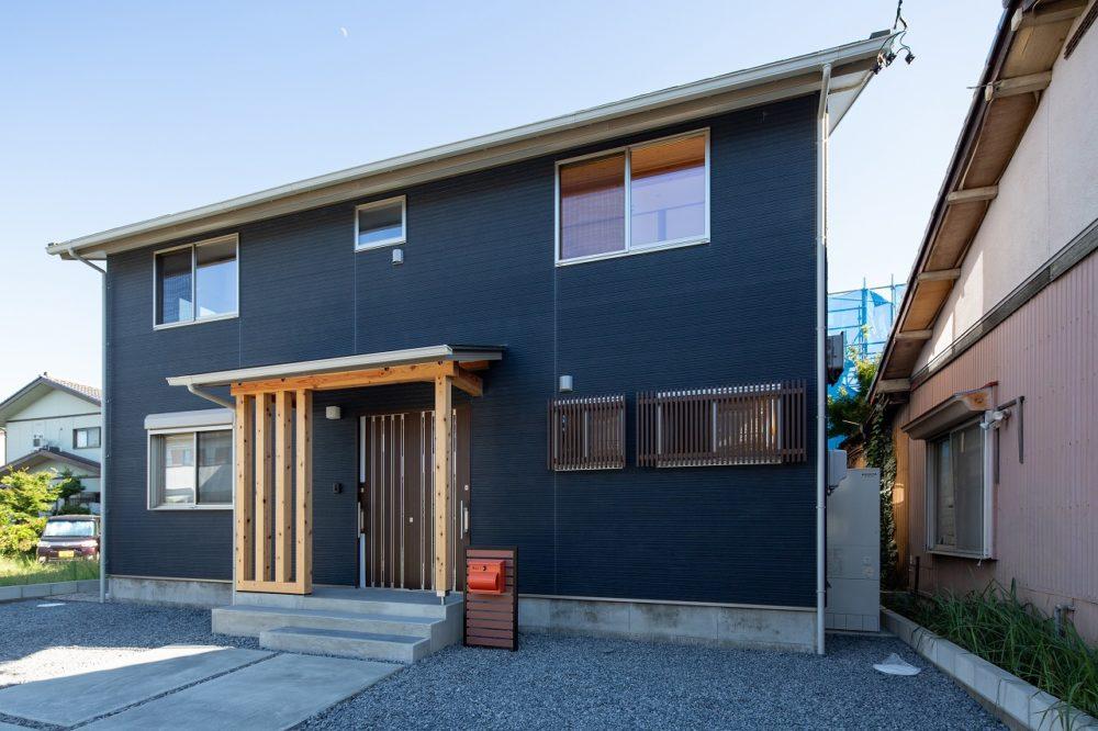 らくらく3台の駐車スペースとアプローチグリーンの瓦と紺色の外壁朱色のポストがアクセント